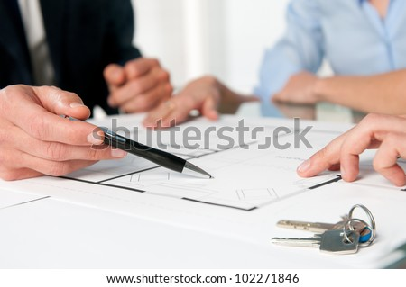 Closeup view of new home keys and house plan during a discussion with a real estate agent