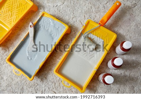 Closeup view of paint tray filled with gray paint. Tools for the painter and redecoration