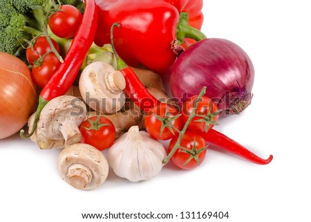 Closeup view of resh farm vegetables including, peppers, tomato, chilli, onions, mushrooms, garlic and broccoli on a white studio background