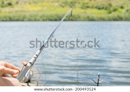 Closeup view of the hand of a man fishing on a lake with a spinning reel and rod looking along the length of the rod #200493524