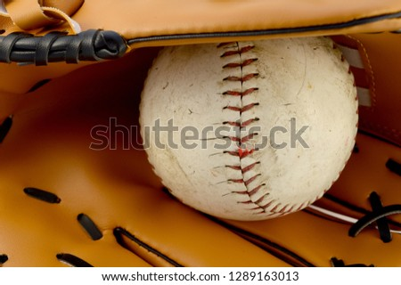 Closeup view of the inside of a baseball glove with a used softball used in team sporting.