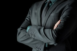 Closeup view of the torso of a businessman standing with folded arms in a classic black suit with a green shirt and necktie, depicting confidence, success and authority.