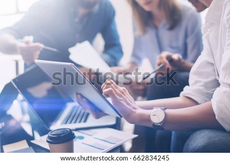 Closeup view of three young coworkers working on mobile laptop computer at office.Young woman holding tablet and pointing on touch screen. Horizontal, blurred background.Cropped #662834245