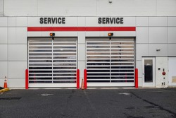 Closeup view of two overhead garage doors with the word service over each on the side of a white building