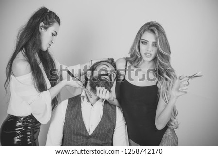 Closeup view of young beautiful people of beautiful fashionable female barber cutting and holding scissors and handsome man with long beard in studio on pink background, horizontal picture