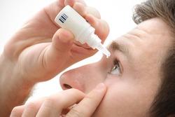 Closeup view of young man applying eye drop