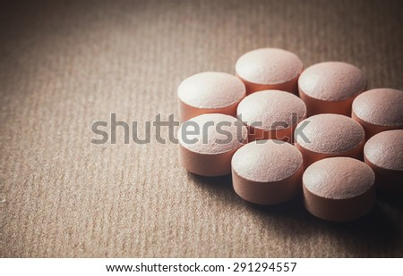 Closeup view on group of pink tablets, blurry brown background with empty space on left side.