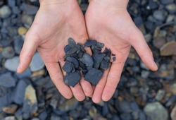 closeup view on hands with pieces of dark  oil shale stones outdoors