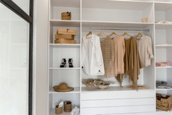 Closeup view on minimalistic modern scandinavian white wood walk in closet with wardrobe in neutral beige colors