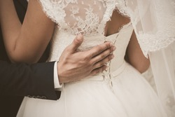 Closeup view photography of back of young bride and male hand of groom hugging waist of woman. Photo filtered in vintage sepia colors.