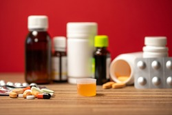 Closeup view photography of orange  syrup medicine in special container cap ad pile of different pills laying near. Many different blurry medical bottles in background.