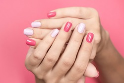 Closeup view photography of two crossed beautiful white hands of caucasian adult woman with trendy asymmetric two colours bright manicure isolated on pastel pink background. Beauty and fashion concept