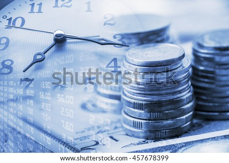 Closeup view : Stack of coins and a clock hands. A concept / idea of time value of money. Money at present time is worth more than the same amount in the future due to its potential earning capacity.