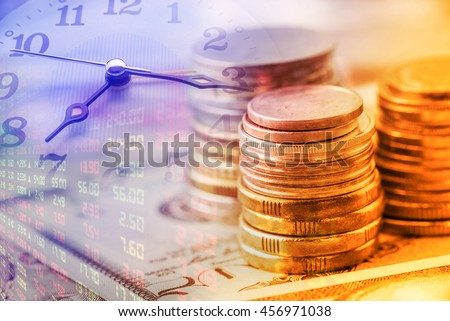 Closeup view : Stack of coins and clock hands. A concept / idea of time value of money. Money at present time is worth more than the same amount in the future due to its potential earning capacity.