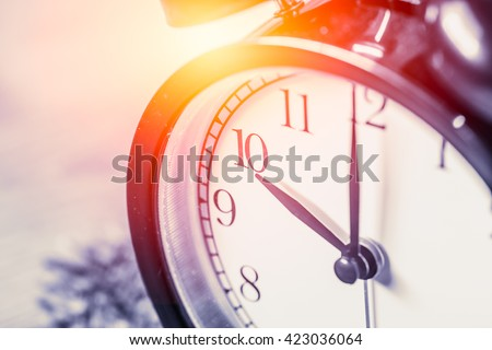 closeup vintage clock selective focus at number 10 o\'clock with sun light vintage color tone for postcard.