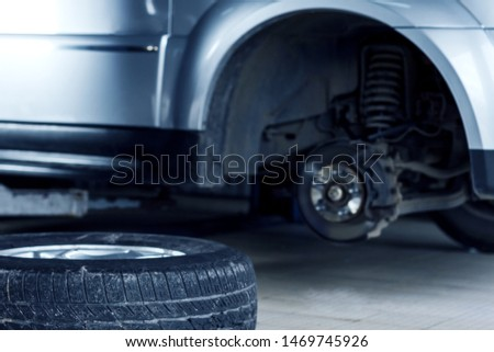Closeup wheel removed from automobile by special equipment, tool. Service station for repairing cars. Workshop auto repair shop for servicing and maintenance vehicle. Tire mounting concept.