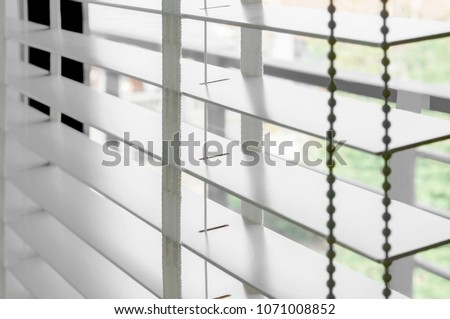Closeup white color wooden blind with white ladder tape curtains.Sunlight through the windows in the city with garden.Selective focus and light image backdrop. #1071008852