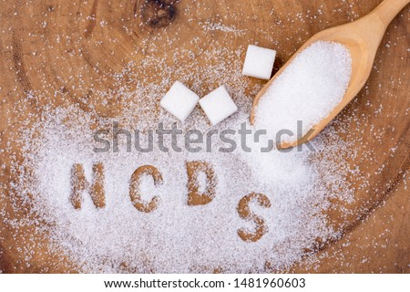 "Closeup white granulated sand sugar in wooden spoon and words""NCDs""  letter written in sugar grains on wood table  background.Unhealthy diet ,awareness and stop NCD  concept. Top view. Flat lay."