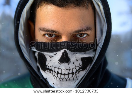 Stock Photo Closeup winter portrait of the man with expressive eyes in the hood and mask with skull - anonymous rebel.