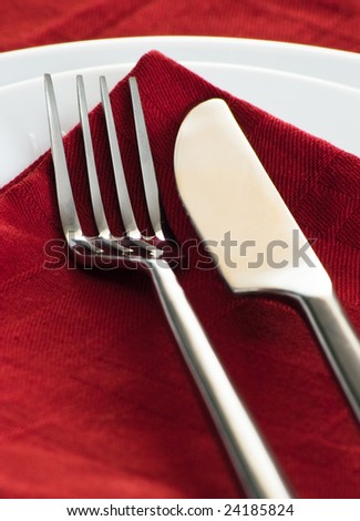 closeup with fork and knife on dark red napkin