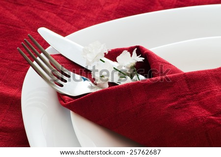 closeup with fork knife and flowers on dark red napkin