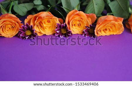 Closeup with free space in the bottom beautiful orange yellow roses purple flowers and leaves composition on the paper background. Colorful floristic wallpapers card picture