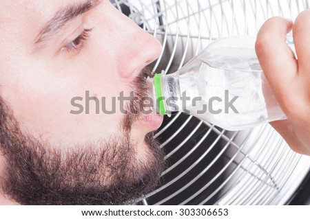 Closeup with thirsty man drinking water  and cooling down with blowing fan