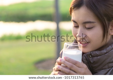 Closeup woman drinking milk with happy face and green nature background, selective focus, healthy care concept - Shutterstock ID 1017313765