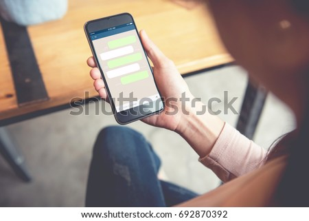 Closeup woman hand holding smart phone, Mock up Blank template chat box for text Chatting and messaging concept #692870392