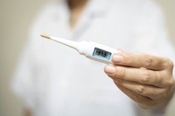 Closeup woman hand holds analogue medical thermometer to  measure the body temperature, protection from virus, flu & respiratory diseases. Coronavirus COVID-19 concept.