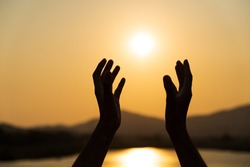 Closeup woman hands praying for blessing from god during sunset background. Hope concept.
