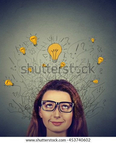 Closeup woman in glasses with many ideas light bulbs above head looking up isolated on gray wall background. Eureka creativity concept