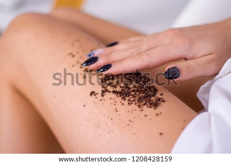 closeup woman legs with coffee massage scrub. Cosmetology, grooming, Spa cosmetic products, beauty and bikini concept.