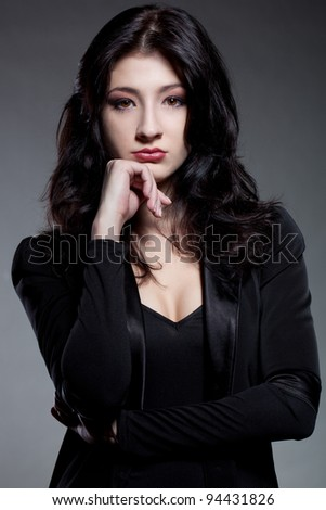 closeup woman portrait with black curly hair and wearing black jacket