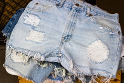 Closeup - women Blue jeans shorts style DIY hole scrape distressed shred for sale in market