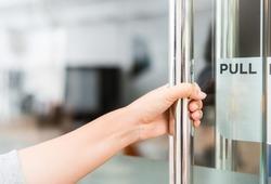 Closeup women hand open the door knob .