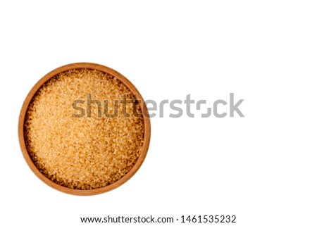 Closeup wooden bowl of granulated brown sugar isolated on white background with clipping path. Unhealthy food concept. Top view, Space for text and content.
