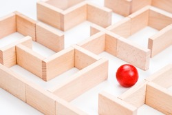 Closeup wooden red ball stuck in the maze game arranged by wood blocks on white background, find a way in business challenge, complicate concept