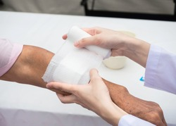 closeup wound dressing An Elderly patient. hand of doctor using bandage covering on senior woman's arm at home, medical and healthcare concept