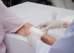 closeup wound dressing infection the An Elderly patient. a using bandage covering on senior woman's arm. wearing clean glove to protect from spreading virus, copy-space medical healthcare concept