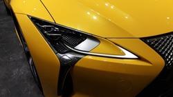 Closeup yellow super car head light,