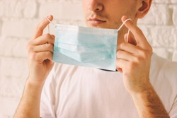 Closeup young professional doctor wearing medical face mask for protection against coronavirus COVID-19. Confident man putting on protective mask on face. Medic holding face mask. Preventive measures