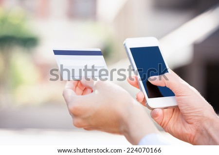 Closeup young woman hands holding credit card and using cell, smart phone for online shopping or reporting lost card, fraudulent transaction, isolated city outside background. New generation gadget