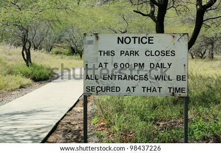 Closing sign along a walking trail in a park.
