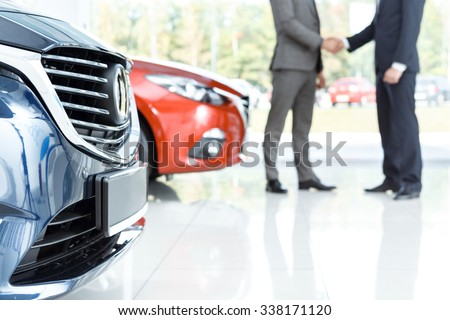 Closing the deal. Selective focus on the car customer shaking hands with dealer on the background #338171120