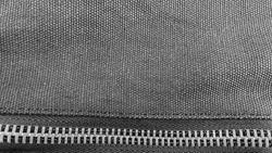 Closure Zip on black fabric handbag background.