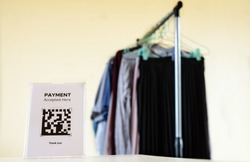 Cloth shop displaying signage of QR code payment. QR code payment is for moblie phone wallet, cashless money techonology, online shopping.