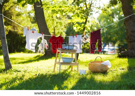 Photo of  clothes and toys hanging on the clothesline in the summer outdoors. accessories to washing