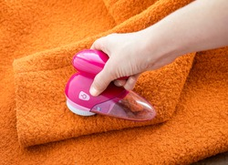 Clothes care. Lint shaver or fabric shaver or fuzz remover in female hand. Woman removing lint on orange wool coat with handheld electric defuzzer.