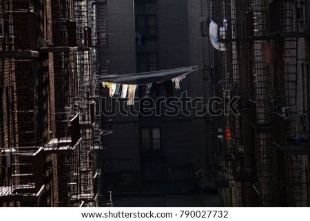 Clothes dry on a line outside of an apartment  #790027732